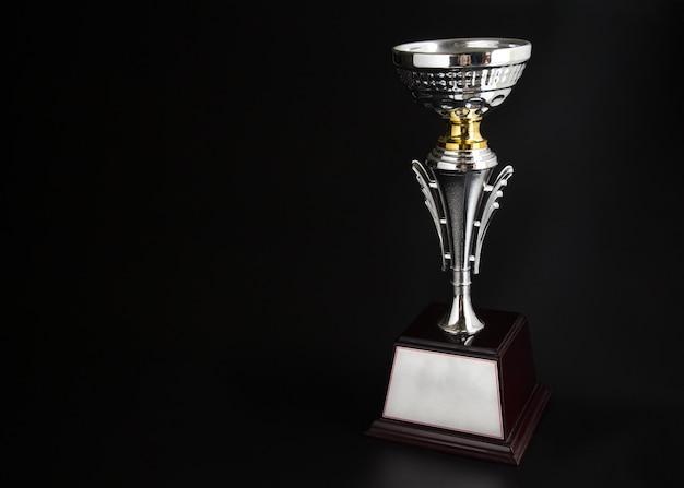 Troféu de prata sobre fundo preto. ganhar prêmios com espaço de cópia de texto e design.