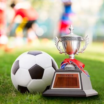 Troféu vencedor e bola de futebol na quadra esportiva de competição