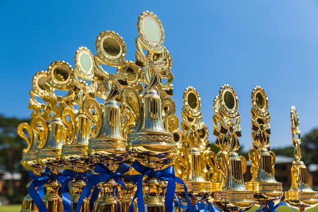 Troféus desportivos na mesa ao ar livre em dia de sol à espera de vencedores para reivindicar seu prêmio