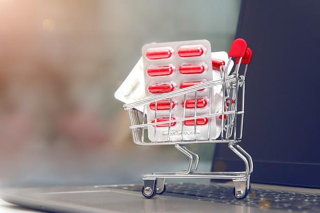 Trole da compra com os comprimidos no fundo do portátil com espaço da cópia. conceito de medicina e compras on-line de drogas. entrega de medicamentos.