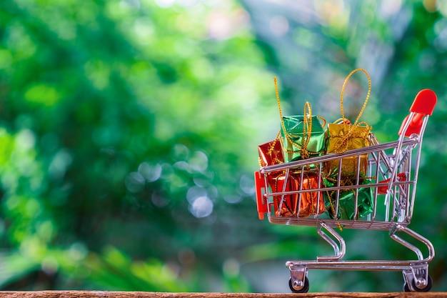 Trole para supermercado ou carrinho de compras e caixas de presente com fundo verde da natureza