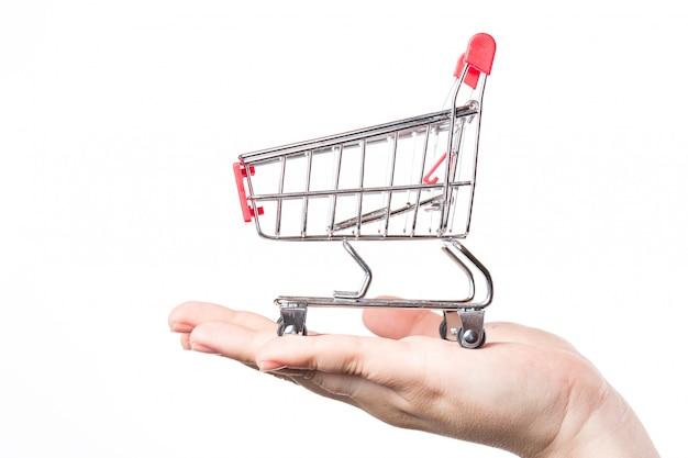 Trole vermelho do carrinho de compras na mão isolado no branco.