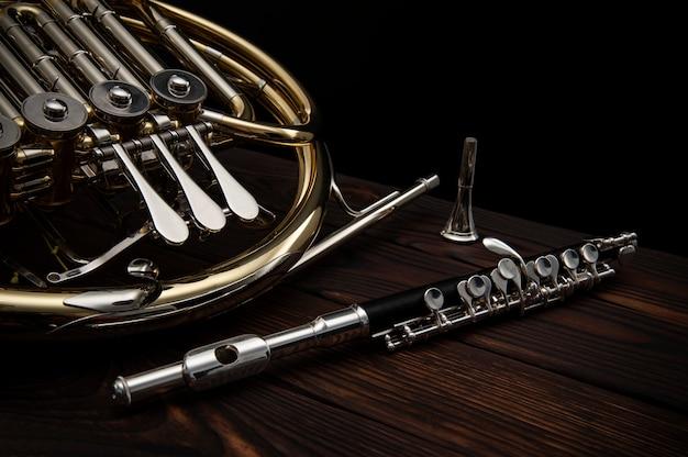 Trompa francesa e uma flauta em uma mesa de madeira