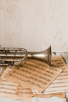 Trompete e partituras perto de parede de madeira