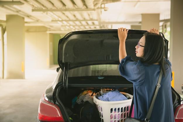 Tronco de carro aberto de mulher no estacionamento