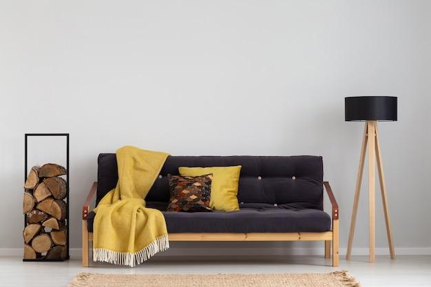 Tronco de madeira ao lado de sofá confortável com cobertor amarelo e almofadas elegante lâmpada de madeira preta