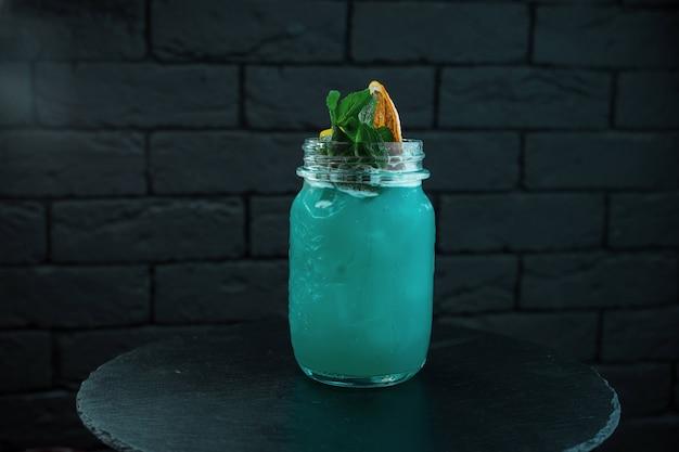 Tropical bright blue sweet cocktail the blue lagoon em um copo de vidro com pedaços de gelo decorado com folhas de hortelã e fatias de laranja está sobre a mesa do bar. vida noturna do clube. bom fim de semana