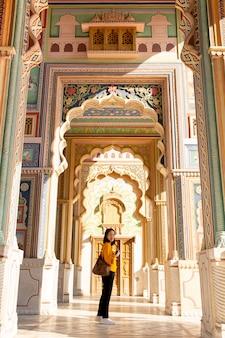 Trourist asiático da mulher que está na porta de patrika índia em jaipur, rajasthan.