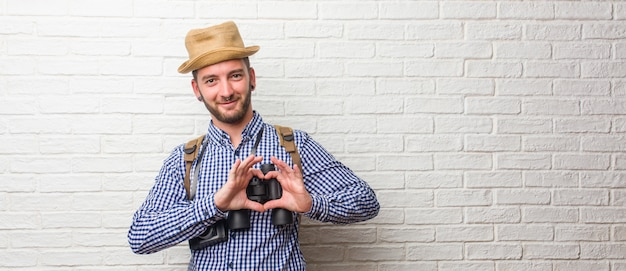 Trouxa vestindo do homem novo do viajante e uma câmera do vintage que faz um coração com as mãos, expressando o conceito do amor e da amizade, feliz e sorrindo. segurando um binóculo.