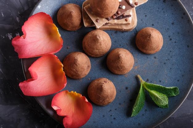Trufa de chocolate com parte de chocolate de leite na placa cerâmica azul. vista do topo