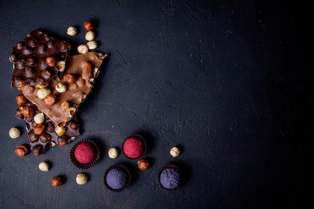 Trufa de chocolate doce com pedaços de chocolate e cacau em pó voando sobre um fundo escuro.