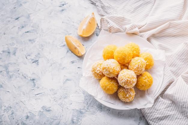 Trufas caseiras de coco e limão veganas cruas. conceito de comida vegetariana. copie o espaço.