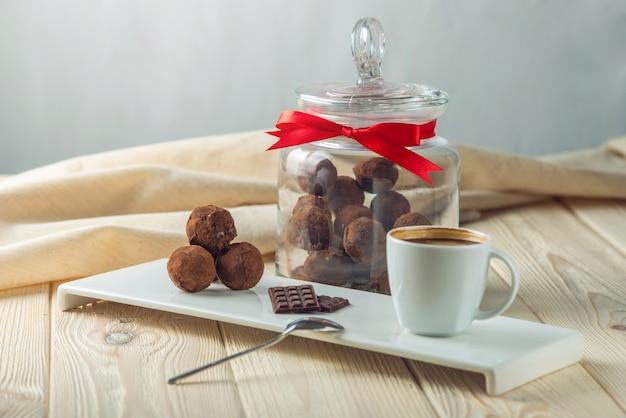 Trufas de bolas de chocolate em um pires ao lado de um pote de doces e uma xícara de café. o conceito de deliciosas sobremesas presentes