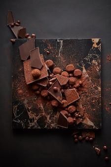 Trufas de chocolate amargo em pó de cacau derramado na placa de mármore escuro