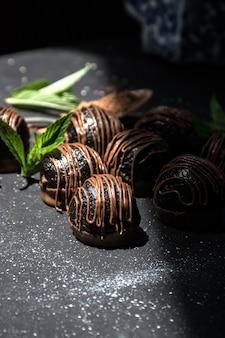 Trufas de chocolate. bombons de chocolate amargo com cacau em um fundo escuro.