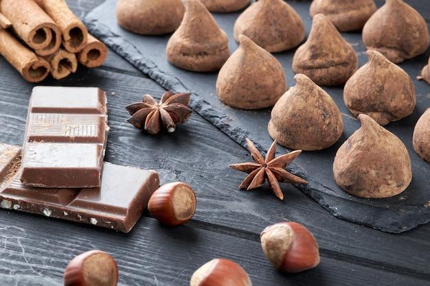 Trufas de chocolate caseiras e chocolate sortido com nozes e outras especiarias na velha mesa da cozinha rústica.