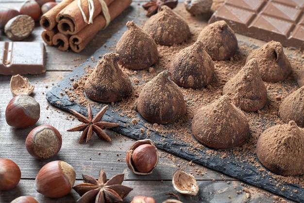 Trufas de chocolate caseiras polvilhadas com cacau em pó e chocolate sortido com nozes e outras especiarias na velha mesa da cozinha rústica.