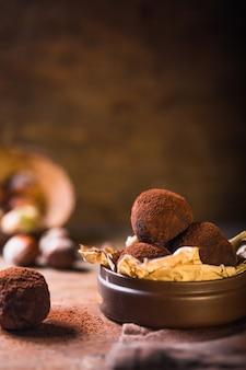 Trufas de chocolate caseiros na opinião de madeira do close up da tabela. saborosos doces vegetarianos ou bolas com cacau em pó cru