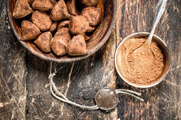 Trufas de chocolate com cacau em pó em fundo de madeira
