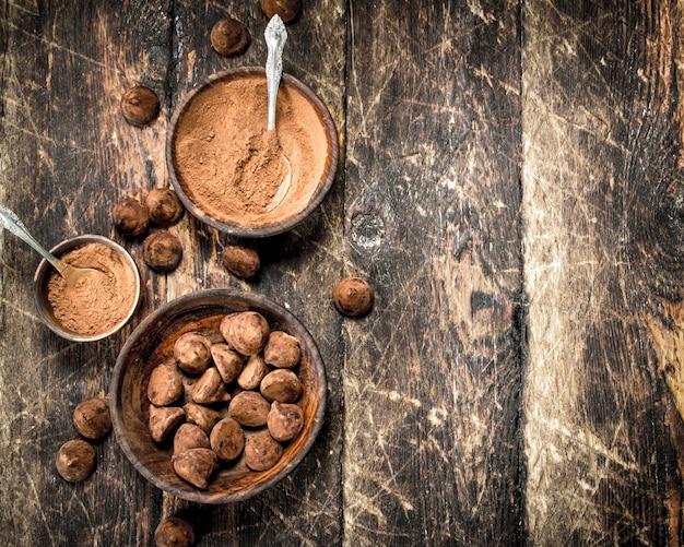 Trufas de chocolate com cacau em pó na mesa de madeira.