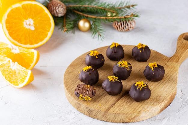 Trufas de chocolate com laranja em um fundo claro