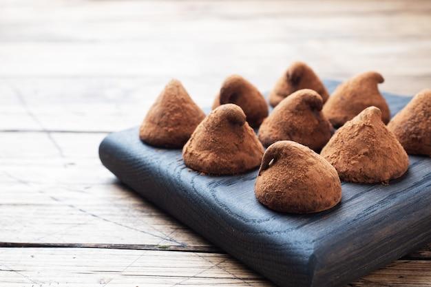 Trufas de chocolate deliciosas polvilhadas com cacau em pó em um carrinho de madeira. fundo de madeira copie o espaço.