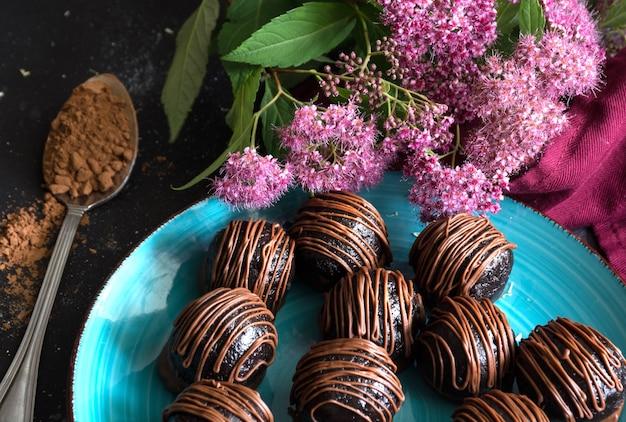 Trufas de chocolate doce e flores cor de rosa em fundo escuro. guloseima deliciosa, sobremesa doce.