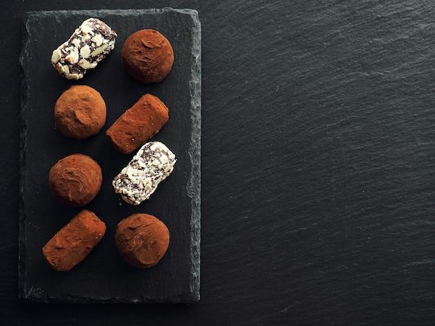 Trufas de chocolate e bombons na mesa escura