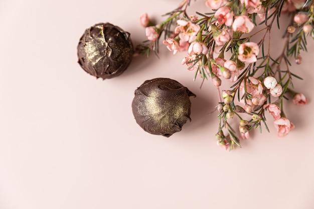 Trufas de chocolate em um fundo rosa decorado com flores rosa