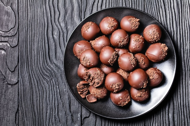 Trufas de chocolate em uma placa preta em uma mesa de madeira texturizada preta, vista horizontal de cima, camada plana