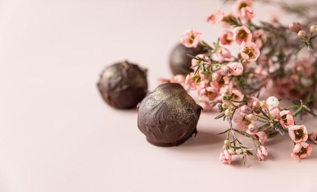 Trufas de chocolate em uma superfície rosa decorada com flores rosa