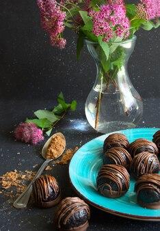 Trufas de chocolate ou doces na placa azul, flores em um vaso em fundo escuro.