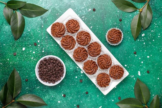 Trufas de mini bolos com gotas de chocolate e cacau em pó, vista superior