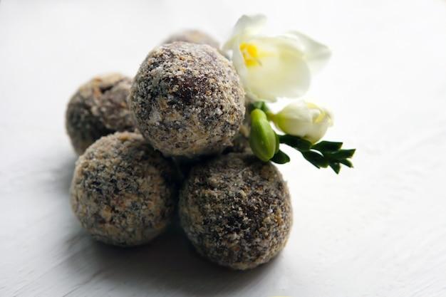 Trufas de rum de chocolate caseiras saudáveis com flor branca em um fundo branco. doces saborosos.
