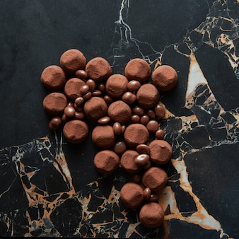 Trufas sortidas de chocolate amargo com cacau em pó e biscoito em uma superfície de mármore escuro