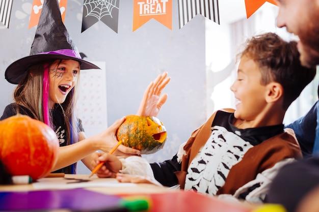 Truques com o irmão. irmã engraçada de cabelos escuros usando chapéu de bruxo, brincando com seu irmão bonito e engraçado