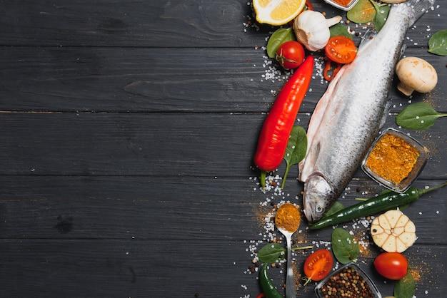 Truta arco-íris fresca com especiarias e ingredientes para cozinhar