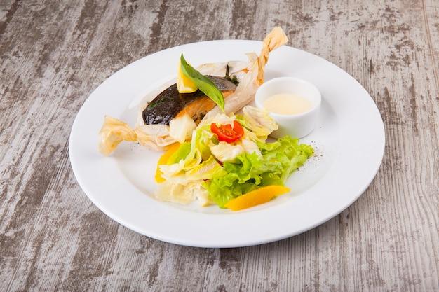 Truta assada em papel com salada e molho branco