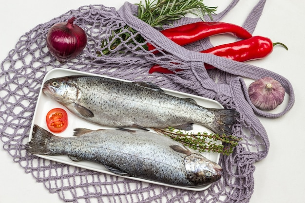 Truta de dois peixes crus na chapa branca. pimenta vermelha e raminhos de alecrim em saco de malha. postura plana.