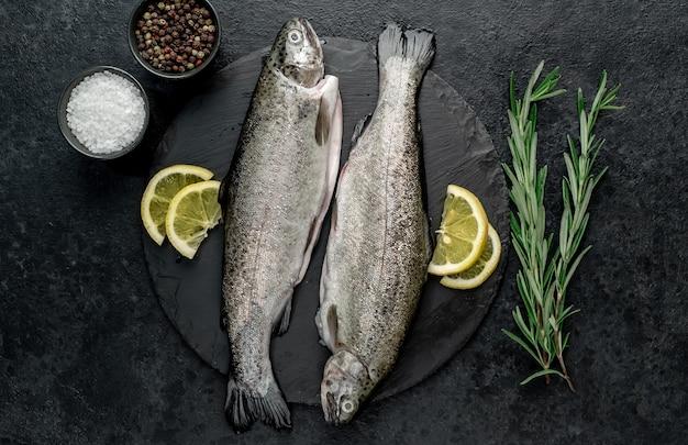 Truta de peixe cru com especiarias prontas para cozinhar em um fundo de pedra