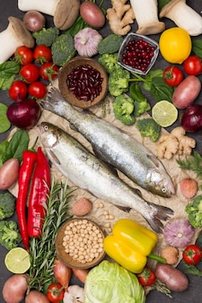 Truta de peixe cru com legumes. couve-flor, grão de bico, alecrim e limão, cogumelos e páprica. postura plana