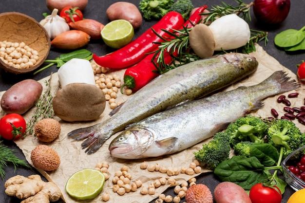 Truta de peixe cru com legumes. couve-flor, grão de bico, alecrim e limão, cogumelos e páprica. vista do topo