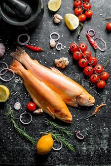 Truta de peixe cru com pimenta, tomate cereja e limão na mesa rústica escura.
