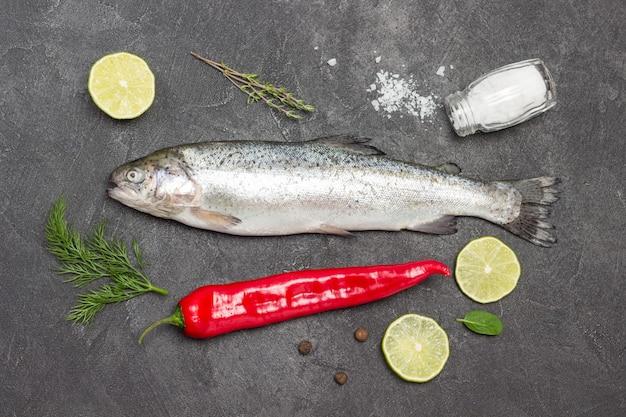 Truta de peixe cru com rodelas de limão e pimenta. postura plana.
