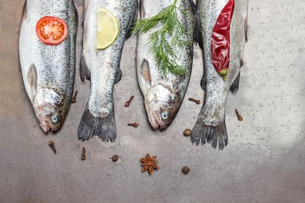 Truta de peixe cru na bandeja de metal. raminhos de alecrim e rodelas de limão, pimenta vermelha. postura plana