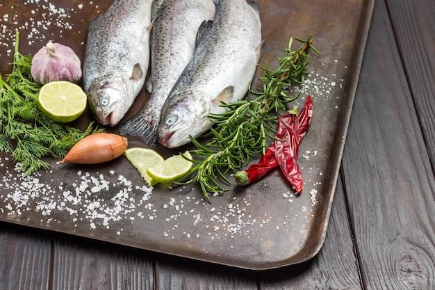 Truta de peixe cru na bandeja de metal. raminhos de alecrim e rodelas de limão, pimenta vermelha. vista do topo.