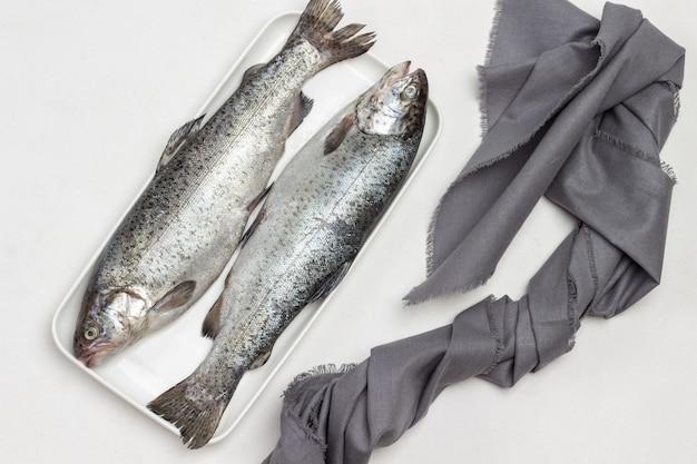 Truta de peixe cru na chapa branca. guardanapo cinza na mesa. postura plana