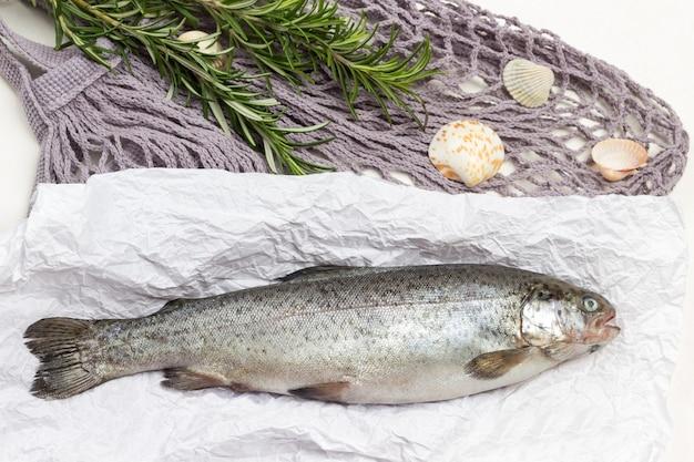 Truta de peixe cru no papel. raminhos de alecrim em saco de malha. fundo branco.