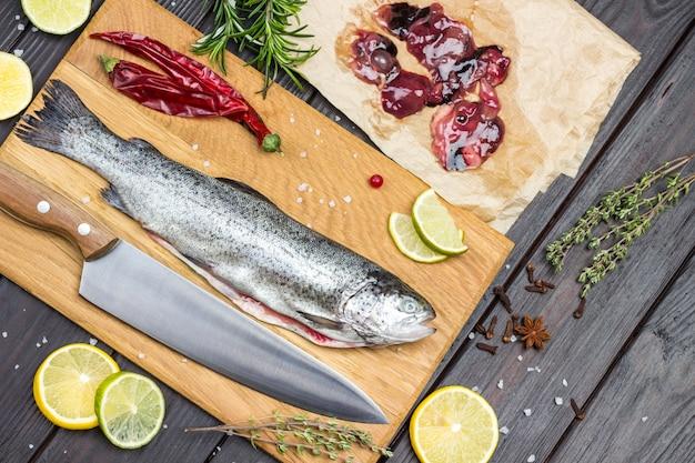 Truta de peixe descascado e faca na tábua. miudezas de peixe no papel. rodelas de limão com alecrim e tomilho na mesa. postura plana
