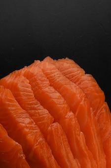 Truta defumada de peixe vermelho salgado em fatias em uma mesa preta. tiro macro. textura salgada do close up da truta fumada. copie o espaço.
